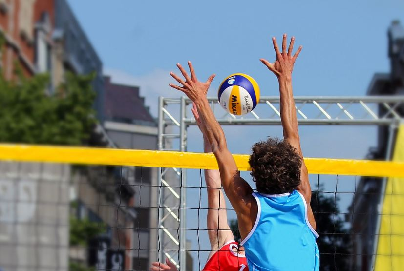 a man trying to block a Mikasa volleyball from another player